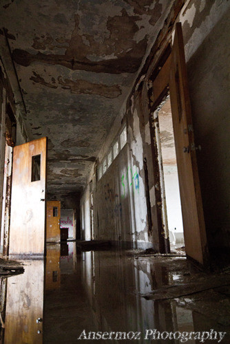 Abandoned school corridor with damaged walls