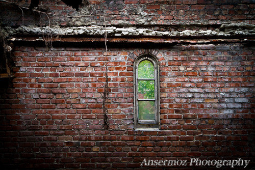Window on a brick wall in abandoned factory