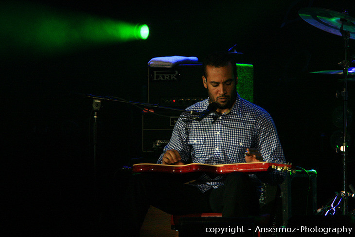 Ben Harper playing slide guitar on stage