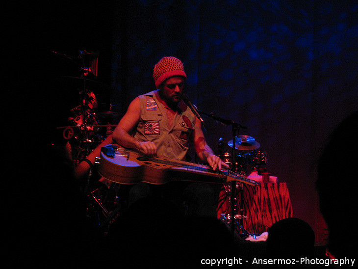 Xavier Rudd playing slide guitar on stage in concert in Montreal