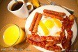 breakfast with coffee, orange juice, bacon, sausages, eggs